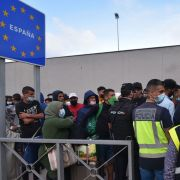Spanish policemen stand next to migrants waiting to cross the border back to Morocco at the Spanish enclave of Ceuta on May 20, 2021.
