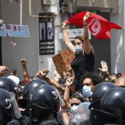 A protester lifts a Tunisian flag at an anti-government rally in Tunis on July 25, 2021.