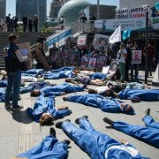 "Extinction Rebellion and Planete Amazone activists stage a ""die-in"" on May 14, 2019, in front of the Grande Arche de La Defense in Puteaux, northwest of Paris."